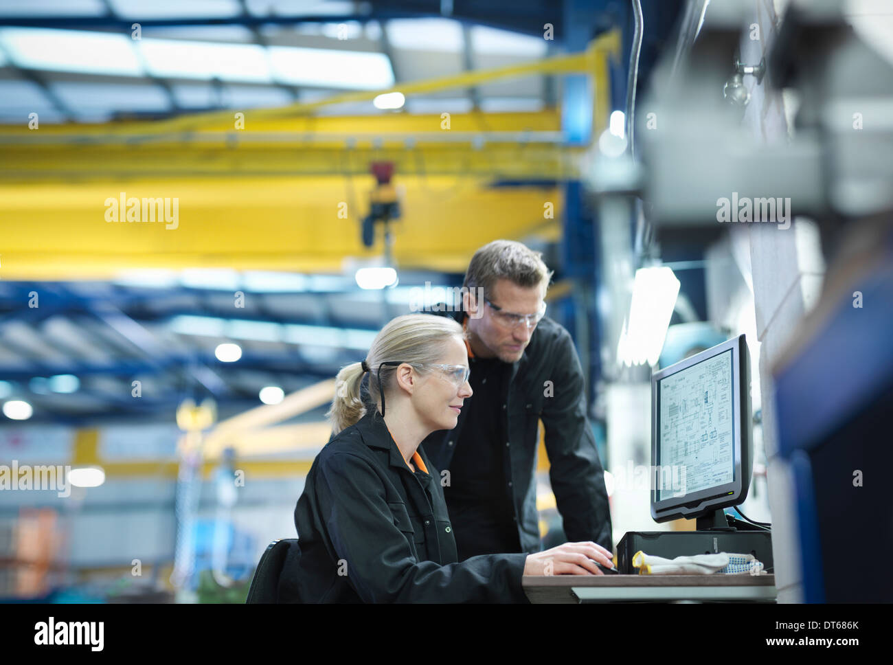 Engineers using computer to work on plans in engineering factory - Stock Image
