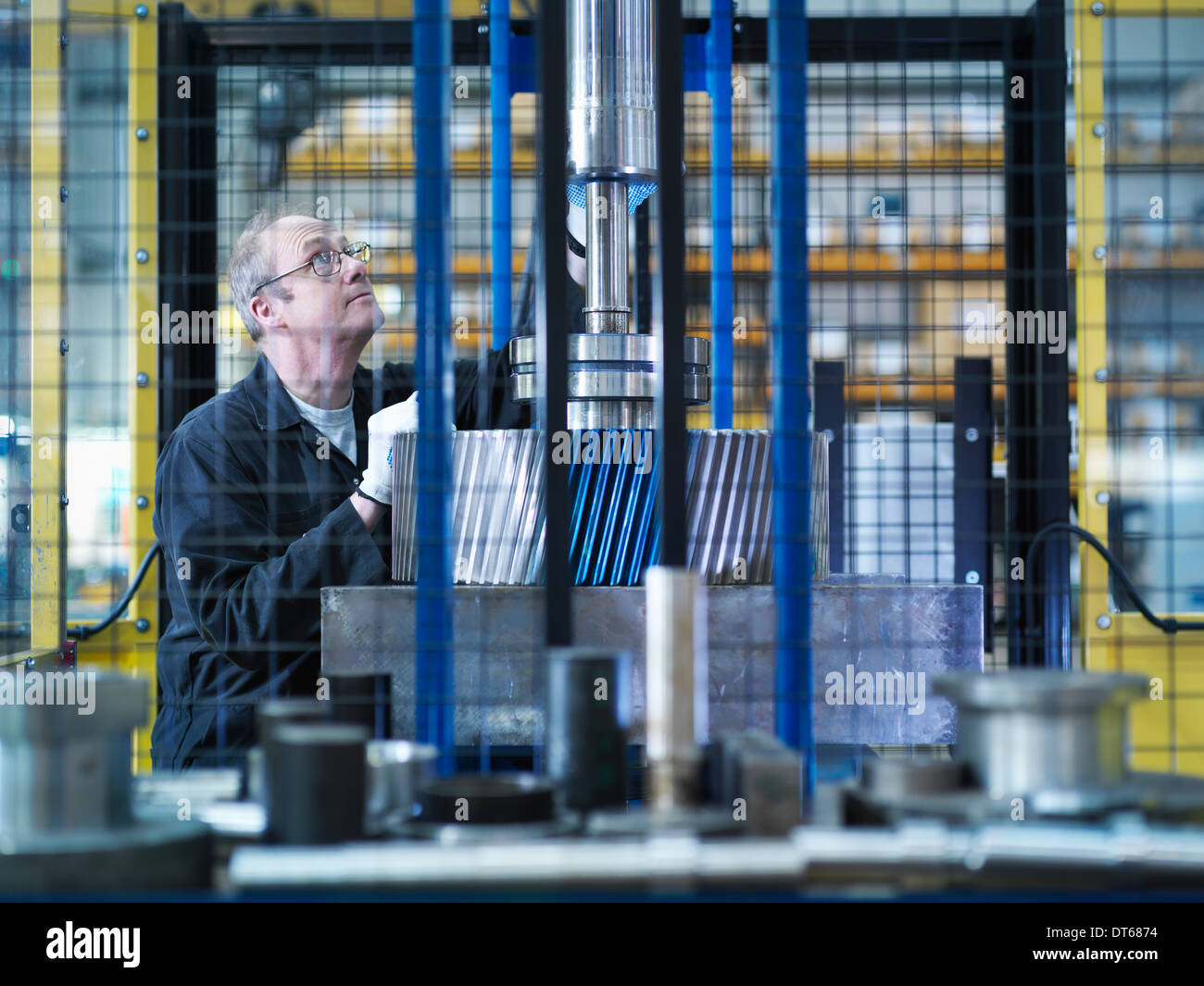 Engineer fixes gear to spindle in engineering factory - Stock Image