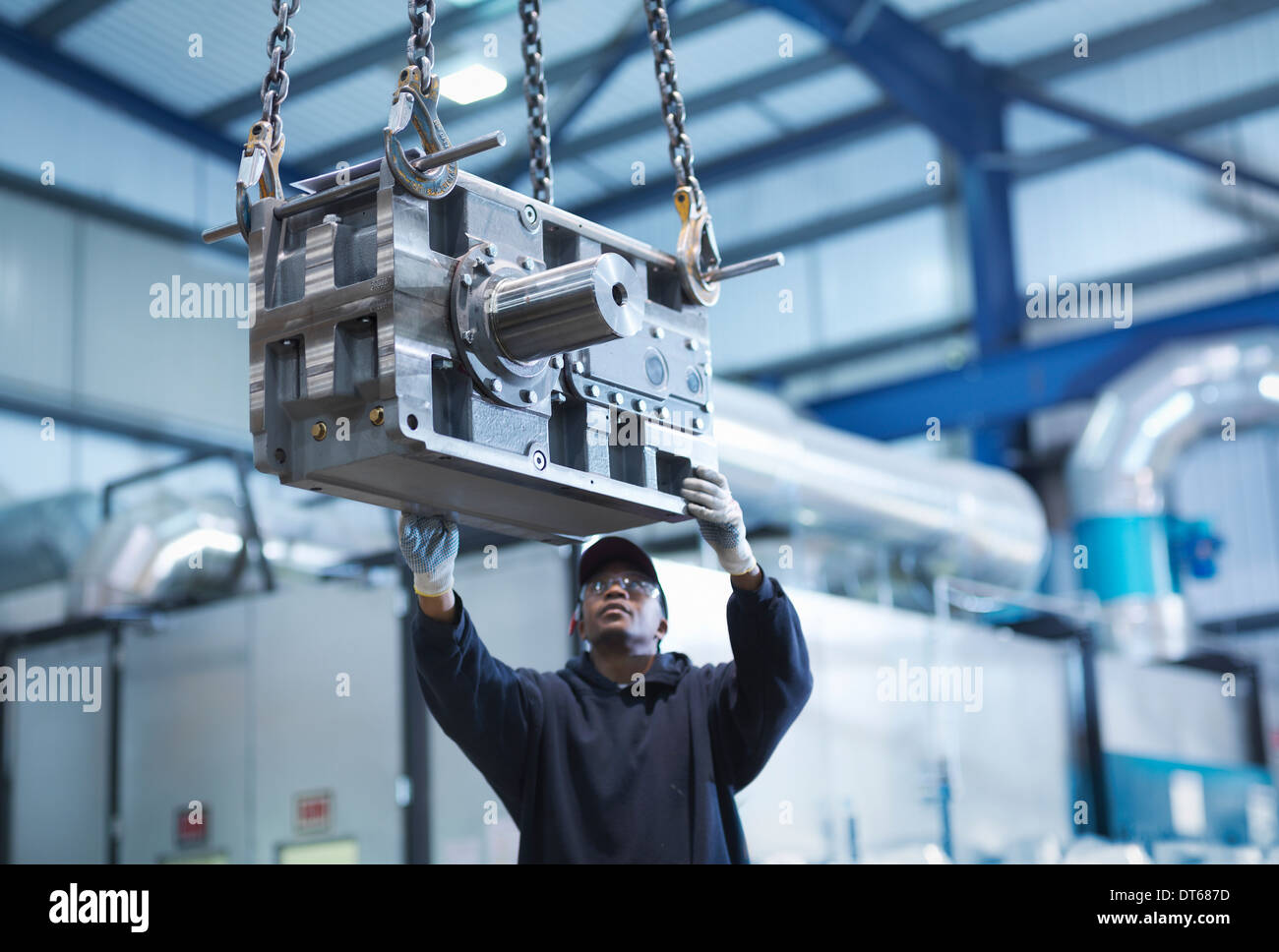 Engineer using crane to move industrial gearbox to paint works in engineering factory - Stock Image