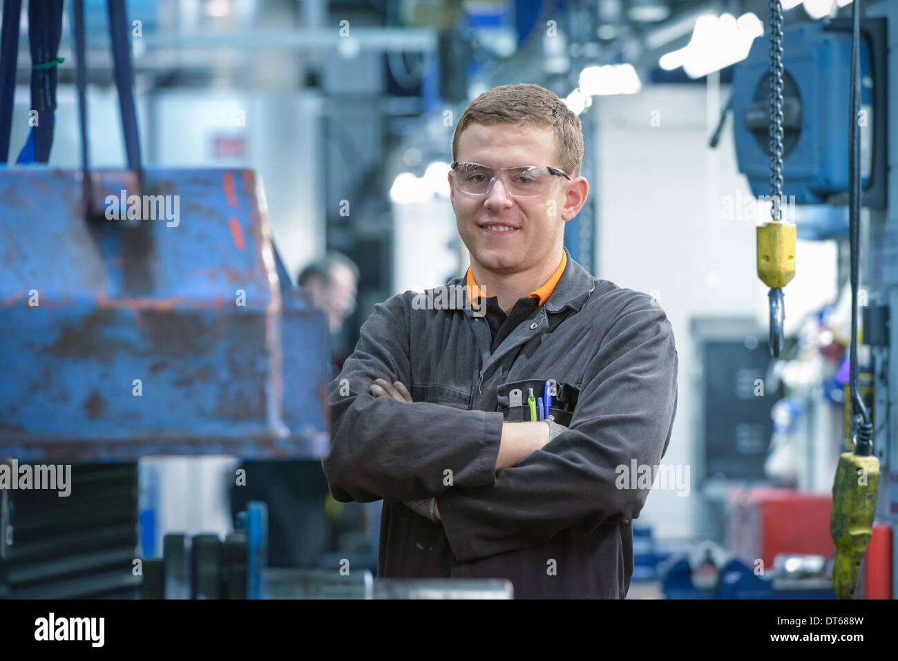 Portrait of engineering apprentice in engineering factory, smiling - Stock Image