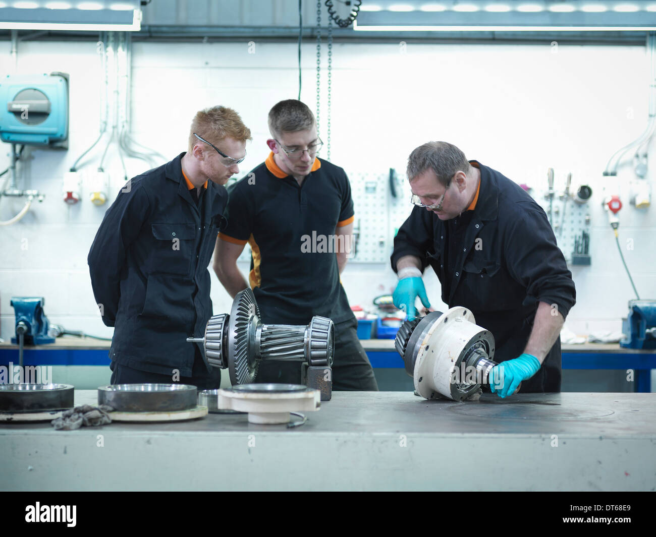 Engineer teaching apprentices in engineering factory - Stock Image