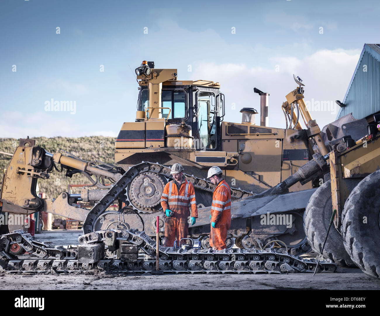Apprentice and engineer work on machinery in surface coal mine - Stock Image