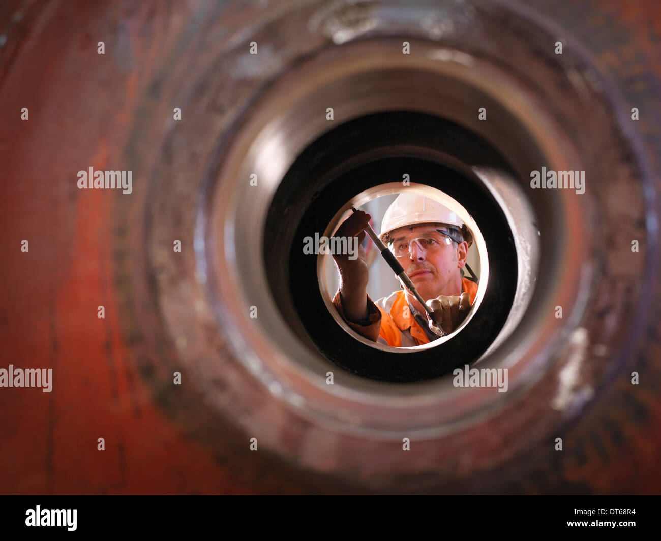 Engineer working on excavator parts in surface coal mine - Stock Image