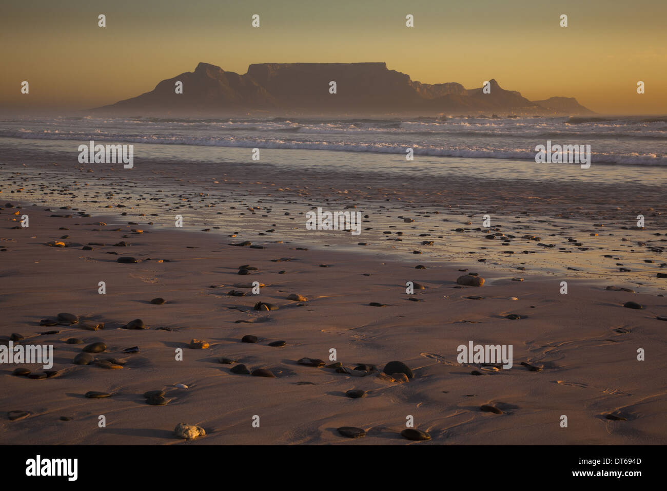Table Mountain and the outline of Devil's Peak and Lion's Head, viewed from the shores of Blouberg beach in Western Cape. - Stock Image