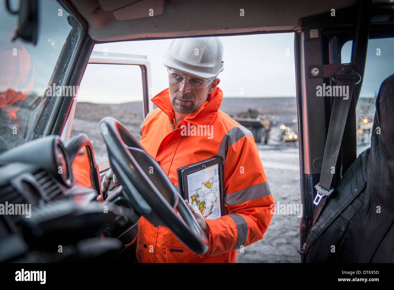Geologist holding digital tablet in truck in surface coal mine - Stock Image