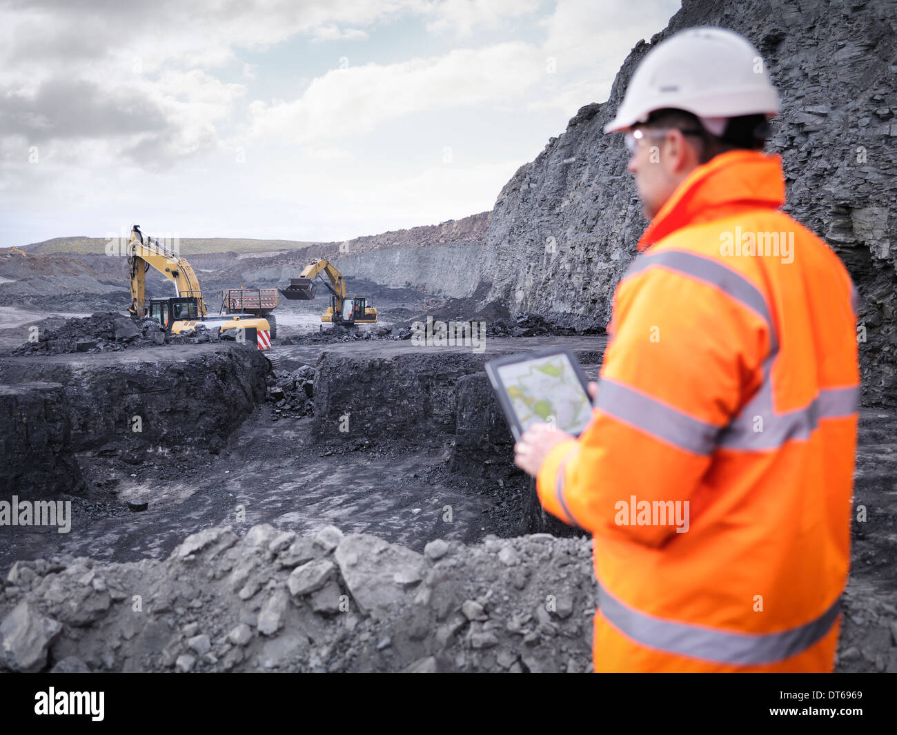 Miner checks plans on digital tablet in surface coal mine - Stock Image