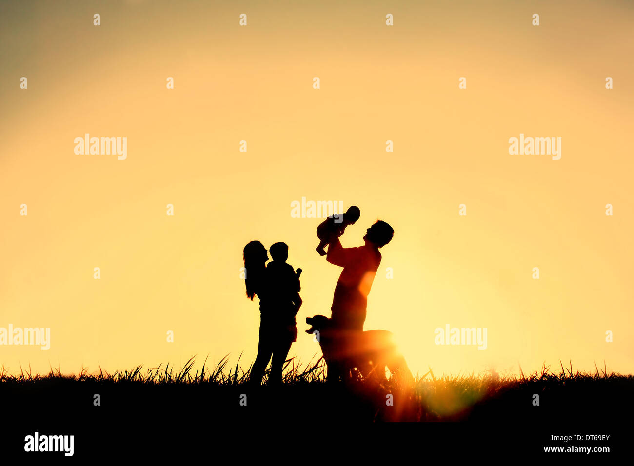 A silhouette of a happy family of four people, mother, father, baby, and child, and their dog in front of a sunsetting sky, - Stock Image