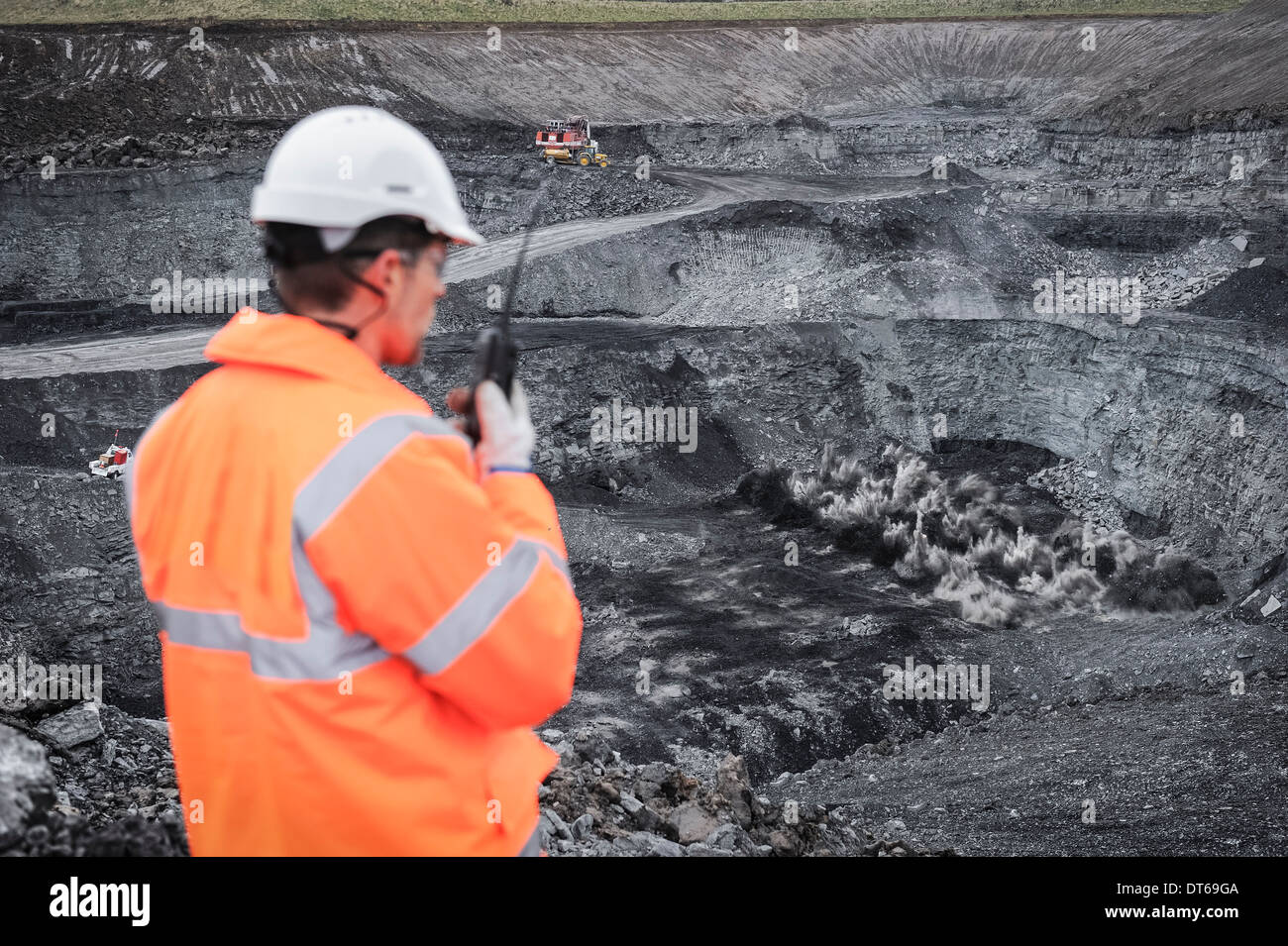 Miner overseeing blasting explosion in surface coal mine - Stock Image
