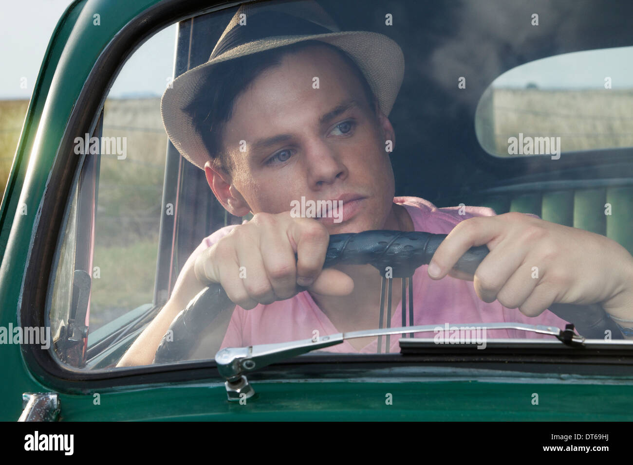 Young man looking through windscreen of vintage morris minor - Stock Image