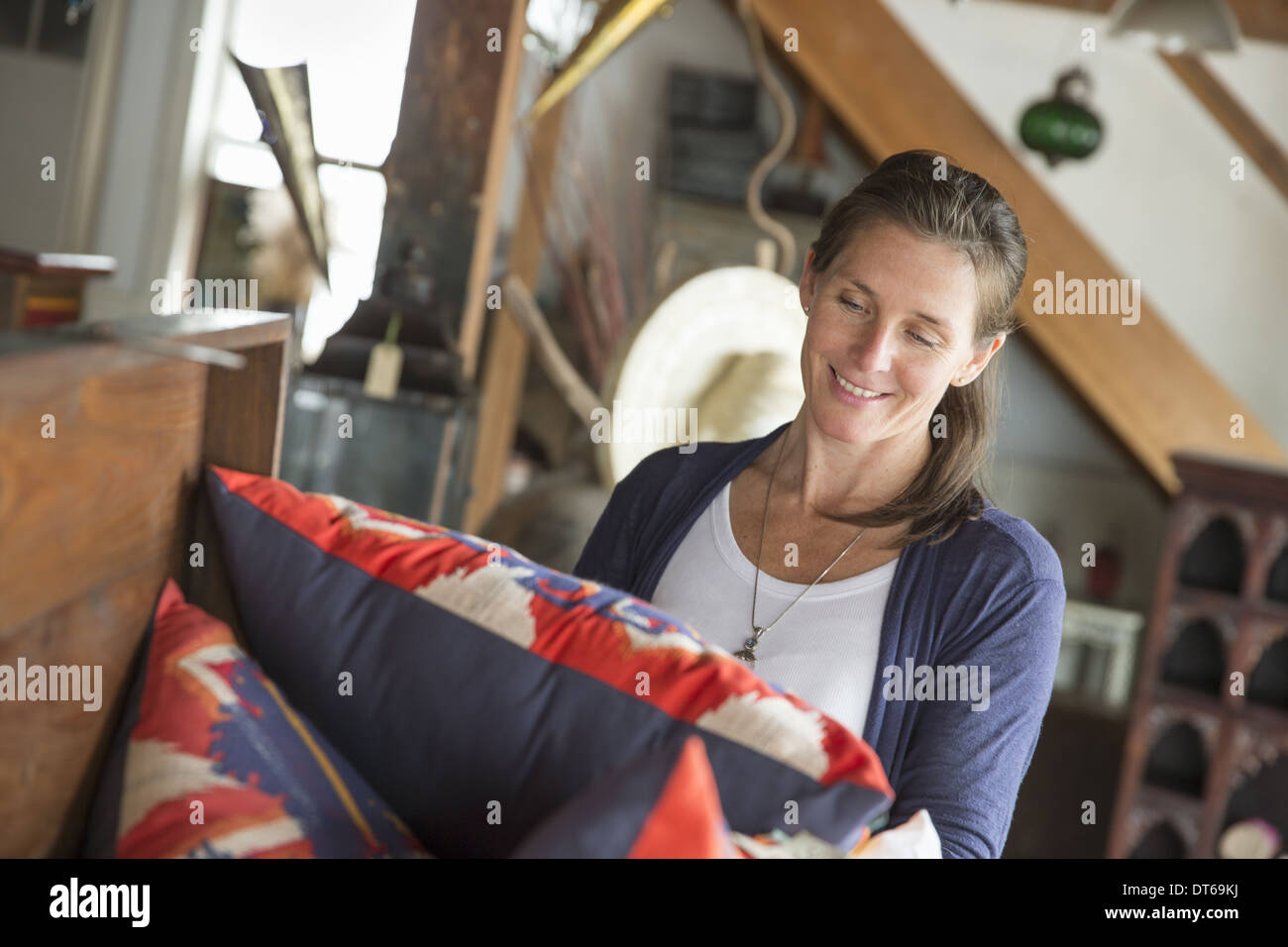 A woman in an antique store in a small town, with objects and furniture from the past. - Stock Image