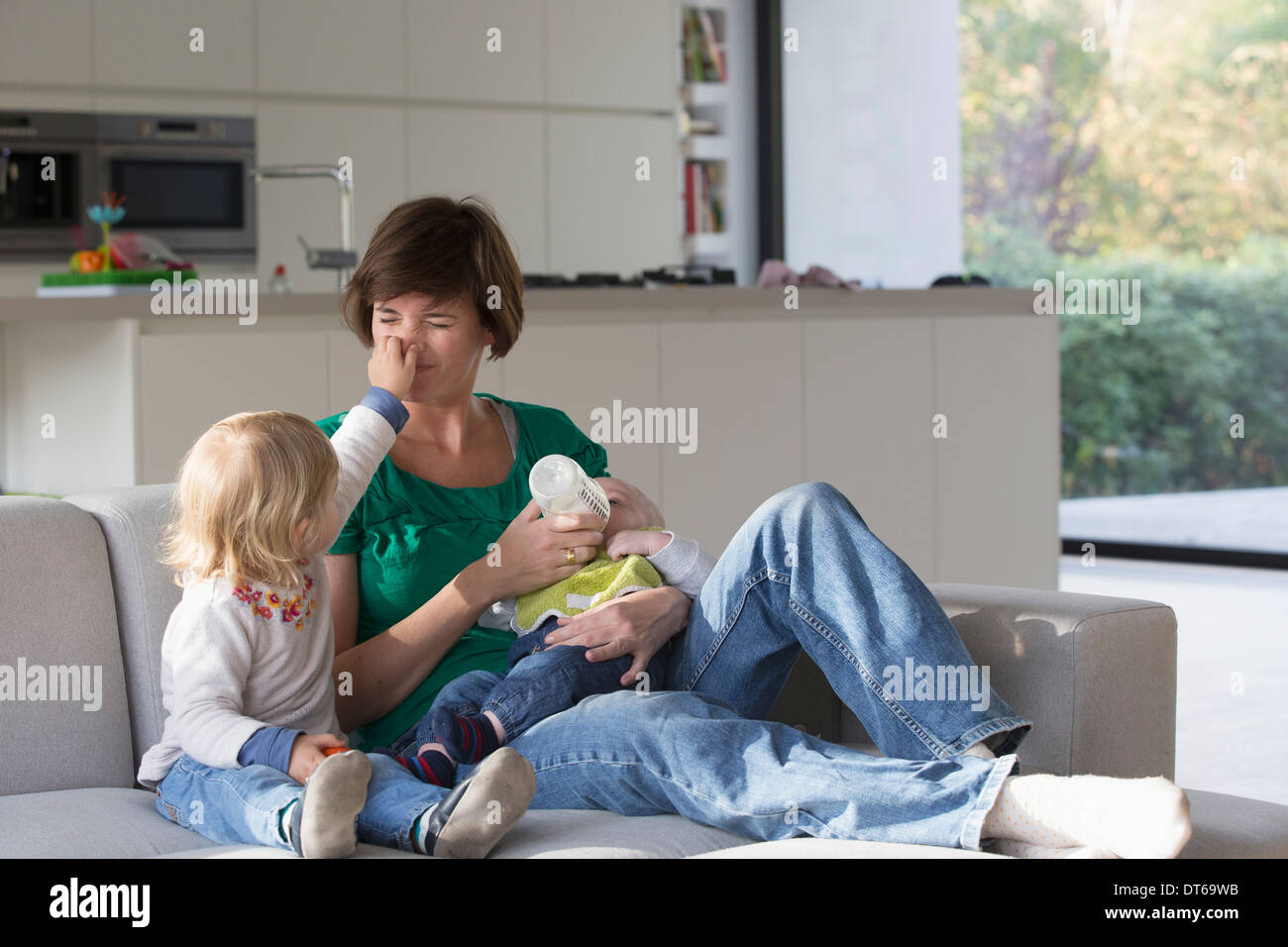 Mother, baby boy and female toddler sitting on sofa - Stock Image