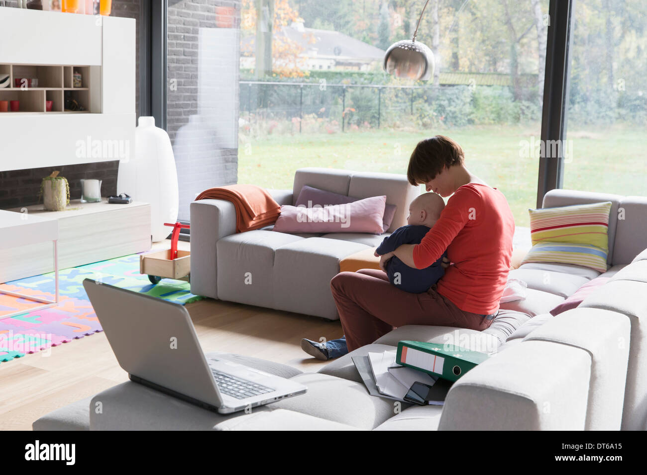 Mother with baby boy sitting on sofa at home - Stock Image