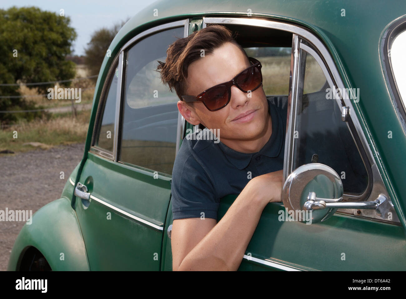Young man leaning out of vintage morris minor - Stock Image