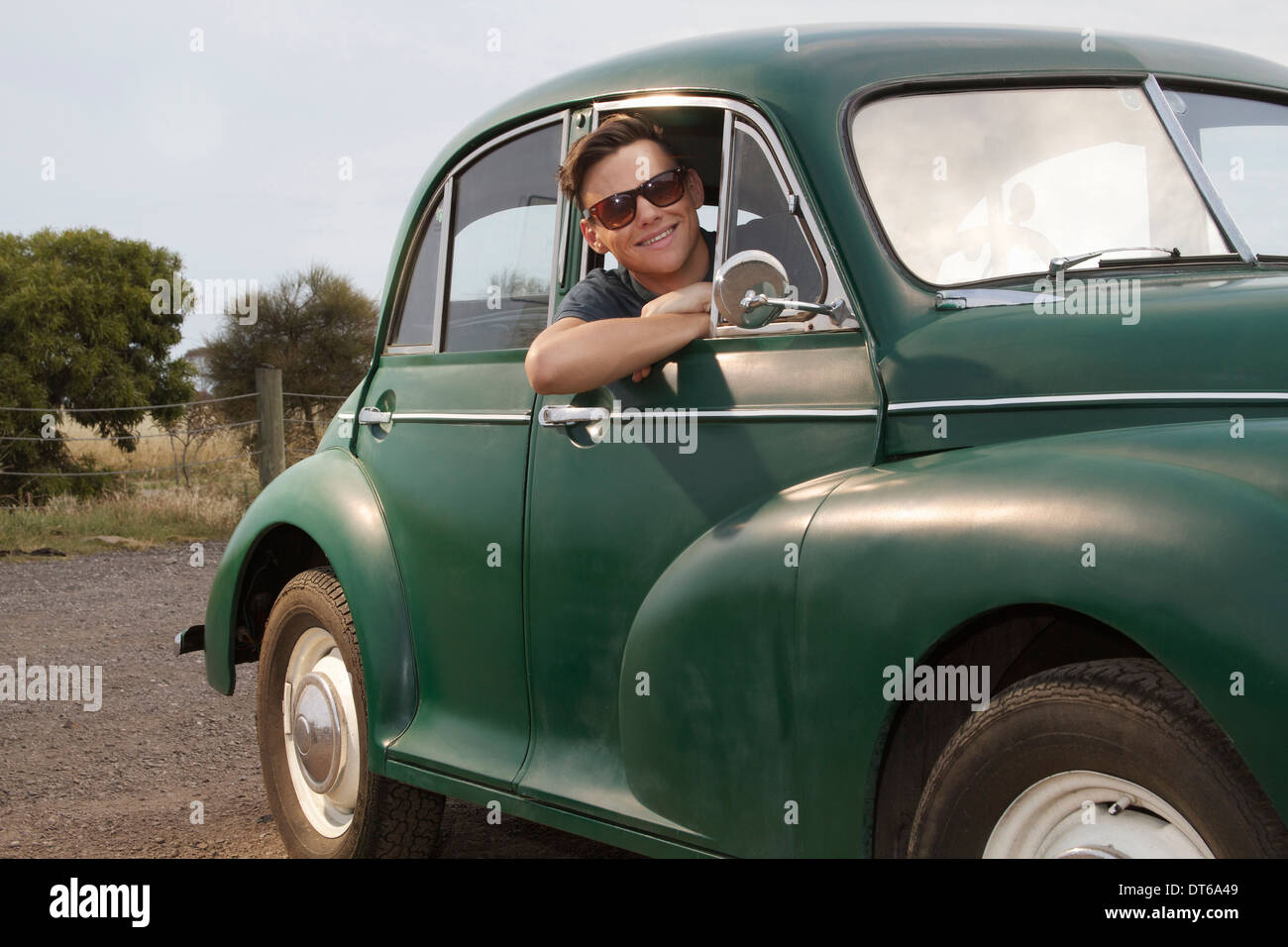 Portrait of young man in vintage morris minor - Stock Image