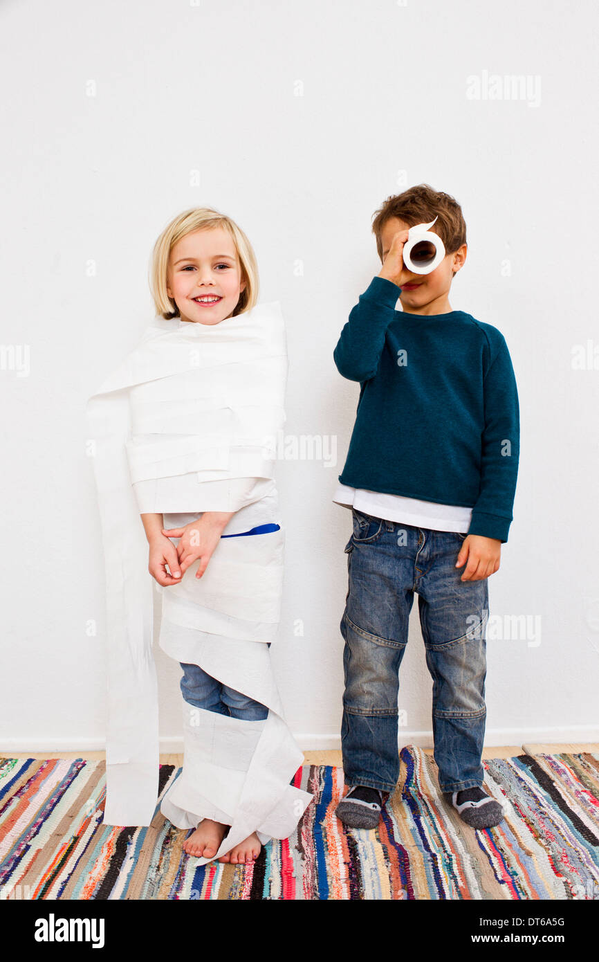 Studio shot of sister and brother with toilet rolls - Stock Image