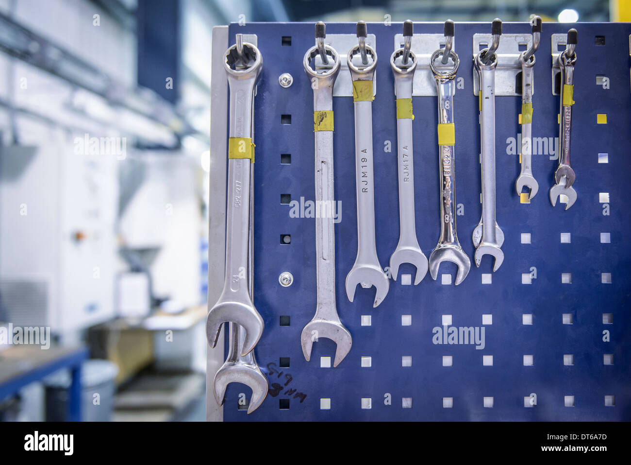 Variety of spanners hanging from workstation rack in factory - Stock Image