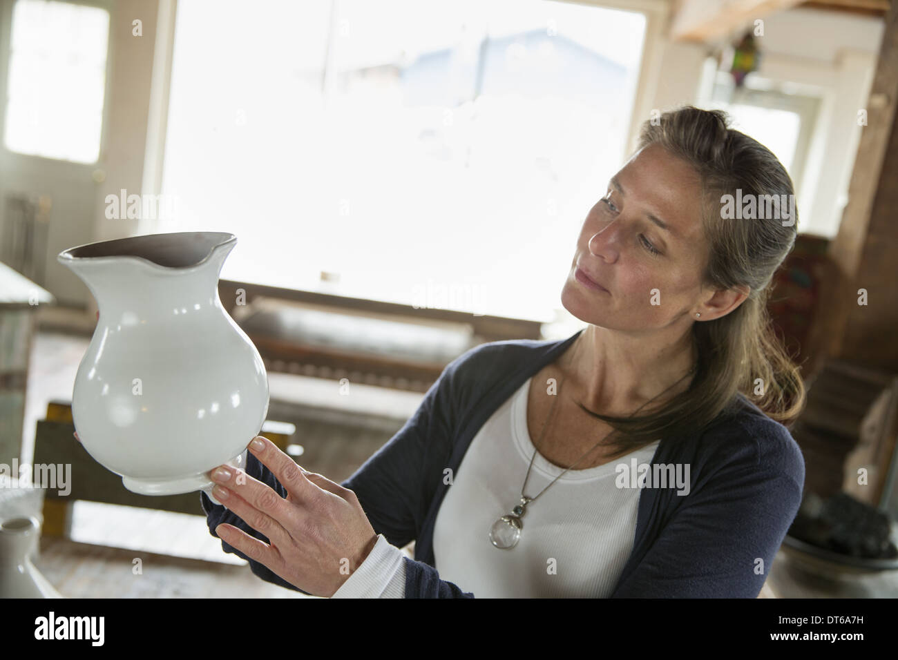 A woman holding a white pottery jug in an antique goods and furniture store. - Stock Image