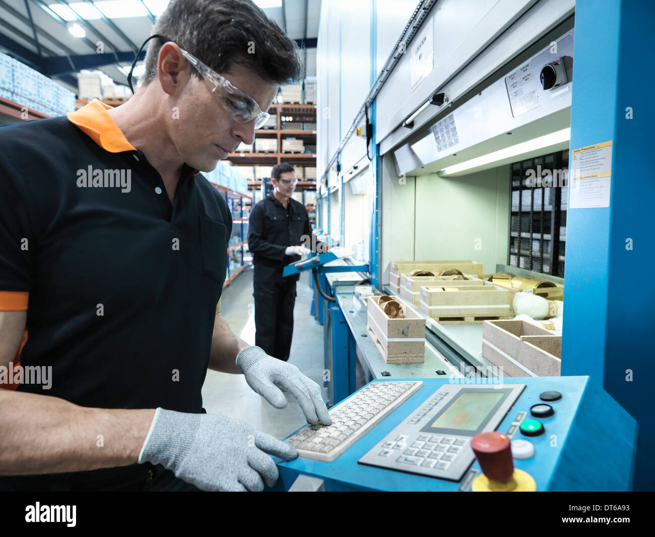 Engineers choose parts from automated store in factory - Stock Image