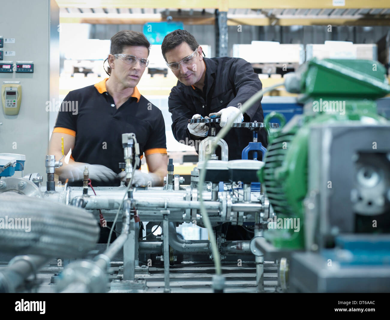 Engineers with industrial pump testing rig in factory - Stock Image