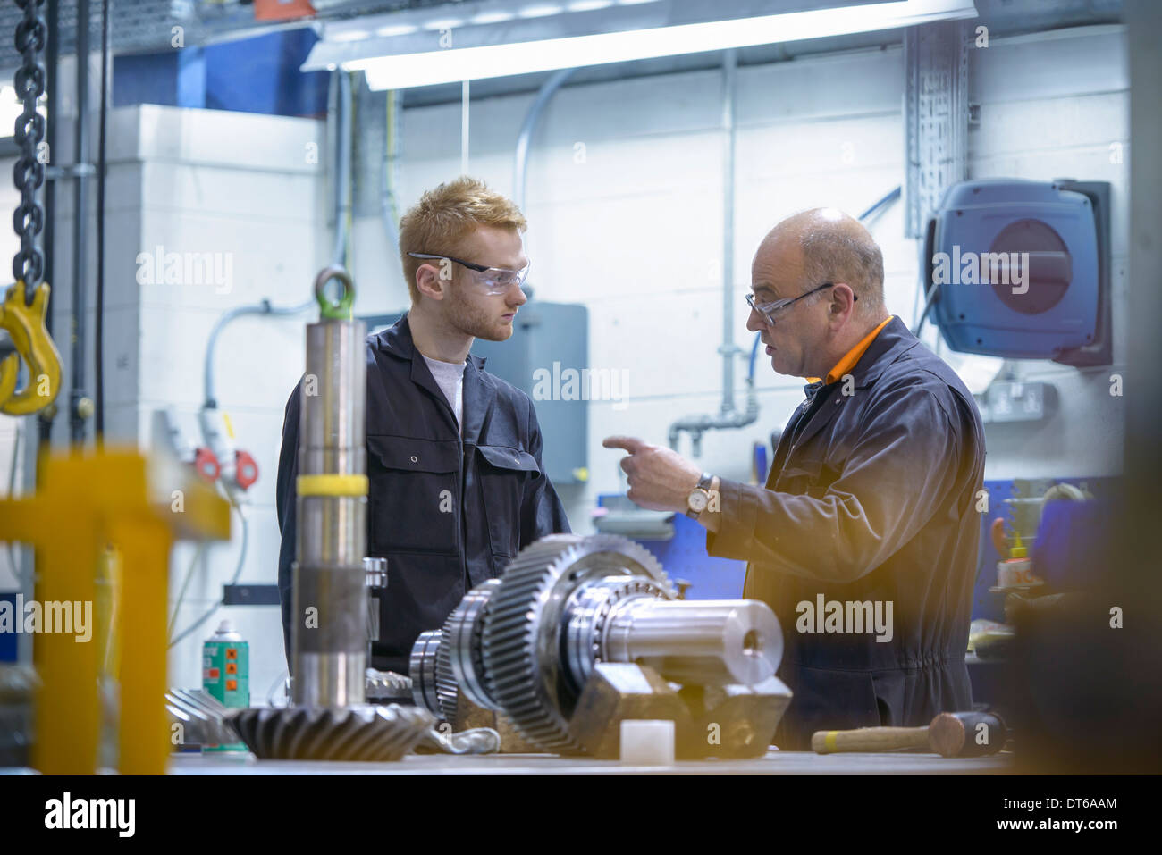 Engineer instructing apprentice at workstation in factory - Stock Image