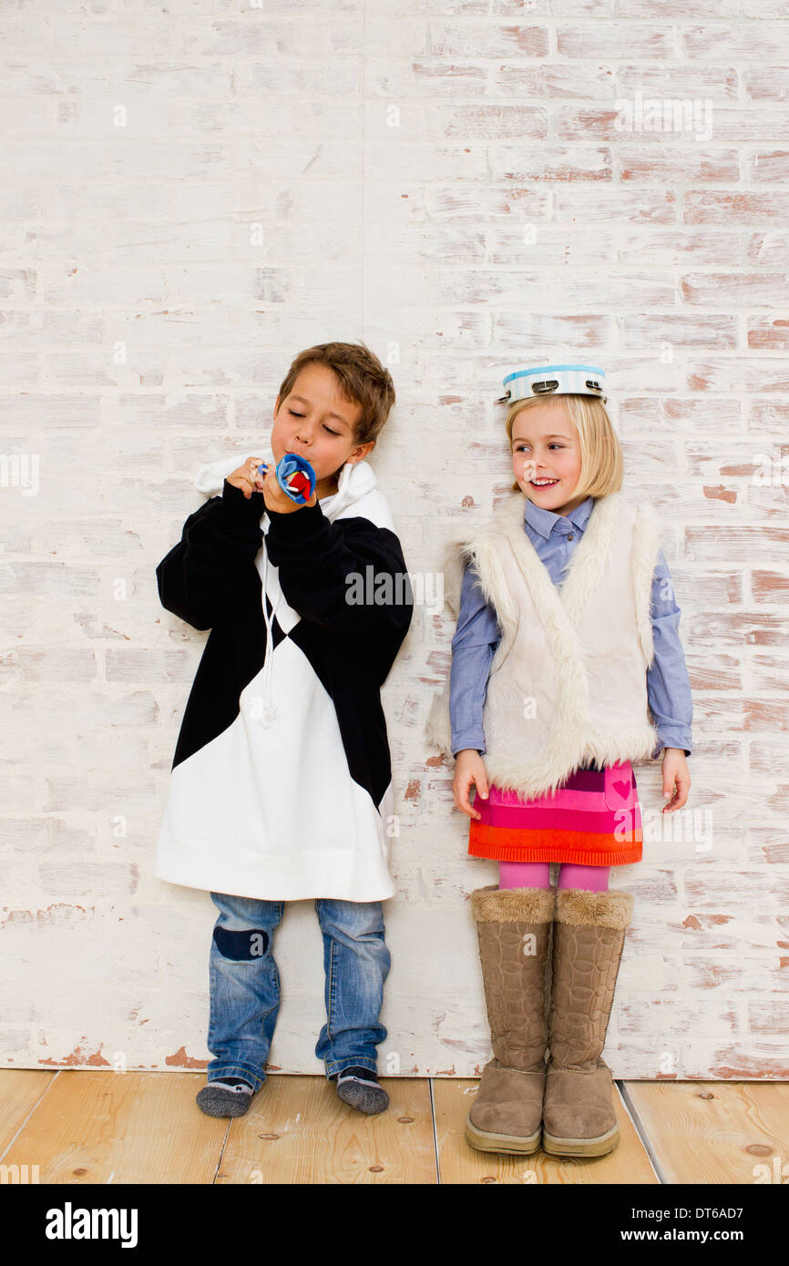 Studio shot of brother and sister in oversize clothes - Stock Image