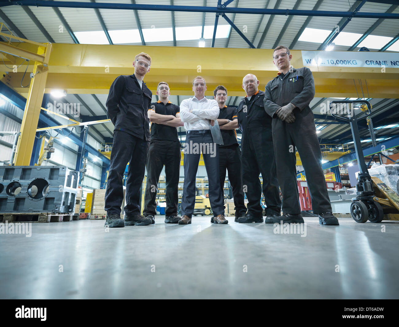 Group of engineers and apprentices in engineering factory, portrait - Stock Image