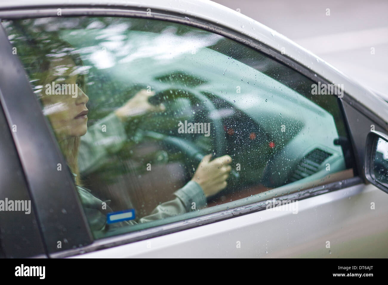 Young woman sitting in car looking out of window - Stock Image
