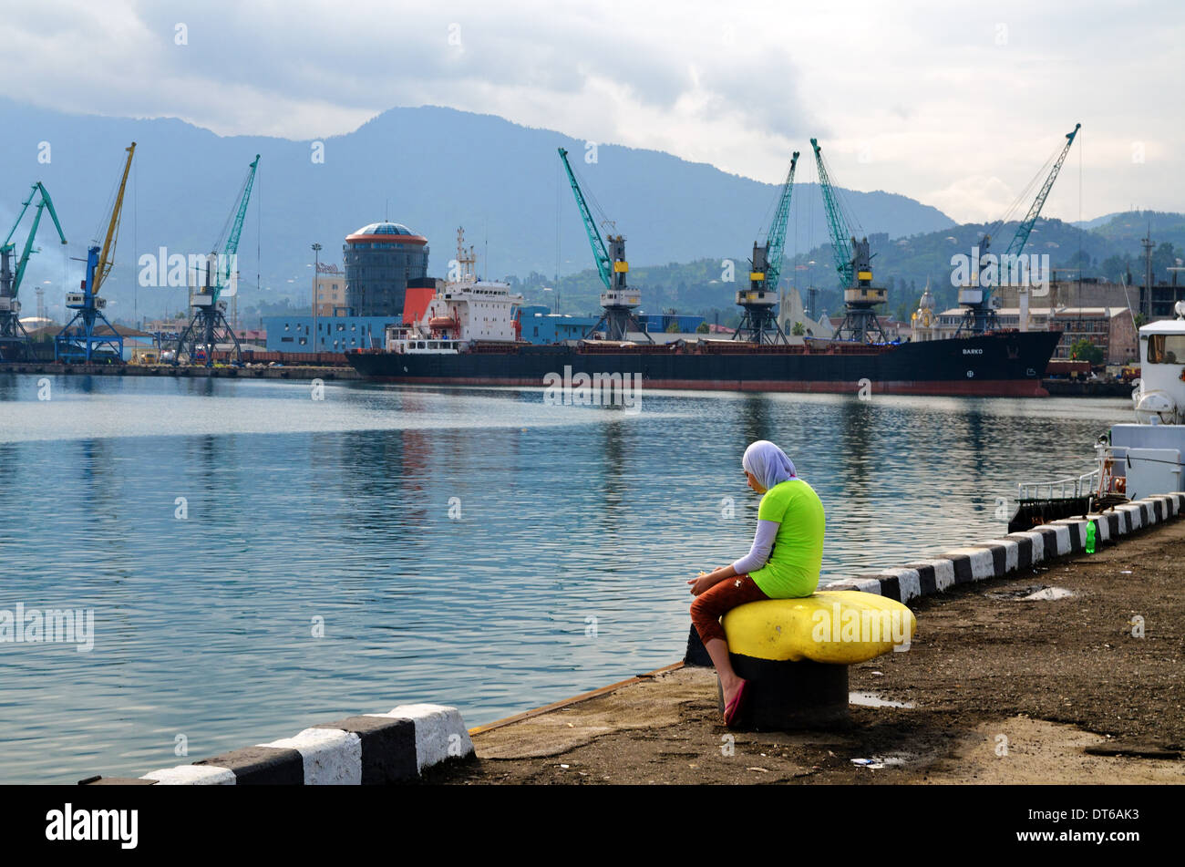 Muslim girl feeds birds on moorage, Batumi, Republic of Georgia - Stock Image