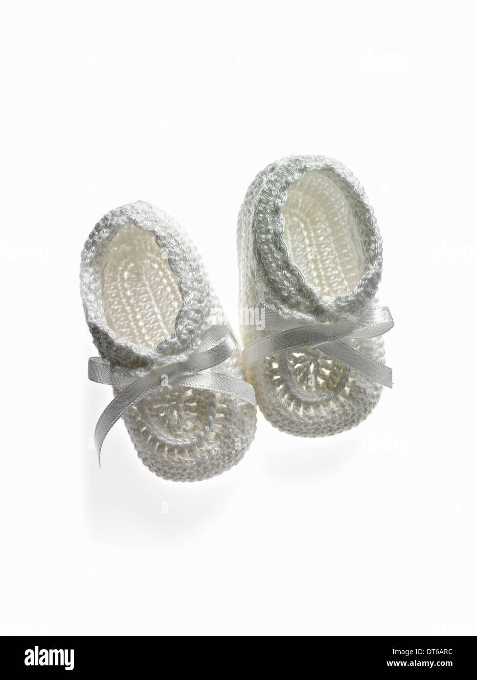 A pair of white baby booties, shoes for infants. - Stock Image