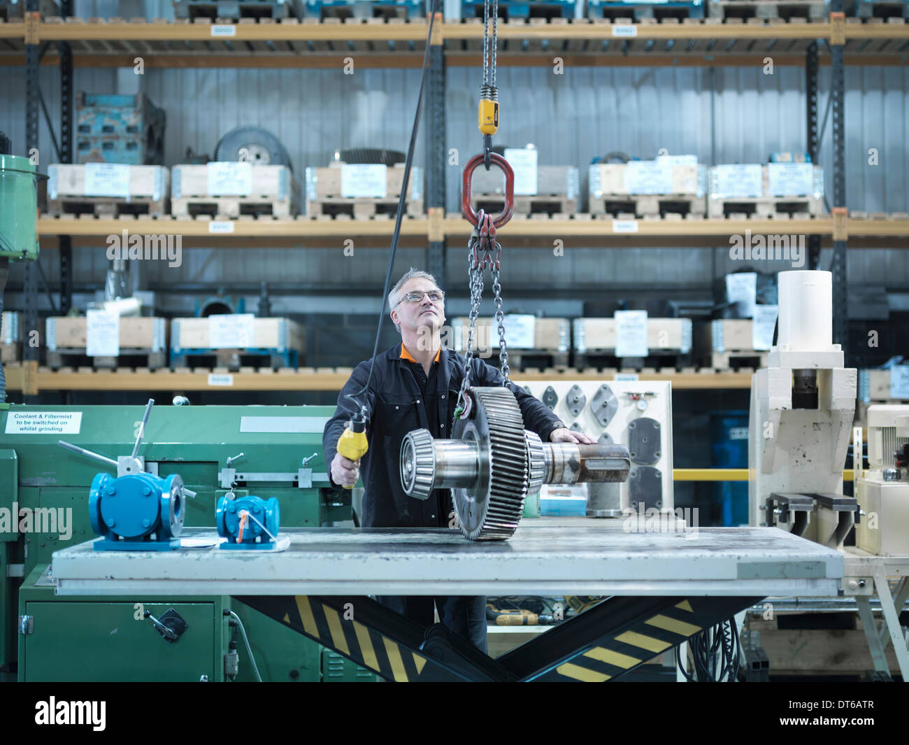 Engineer with gear wheel at work station - Stock Image