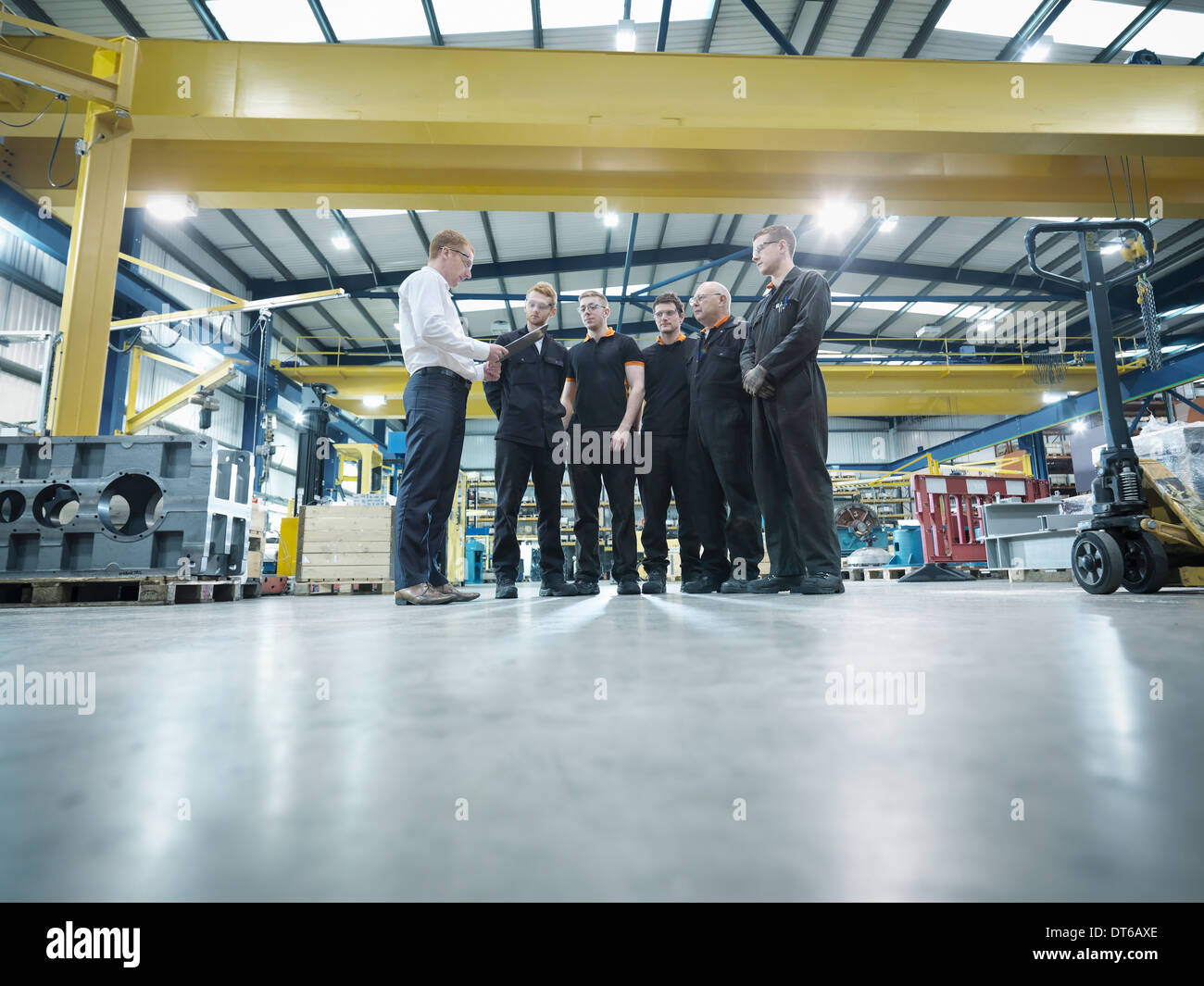 Group of engineers and apprentices in engineering factory - Stock Image