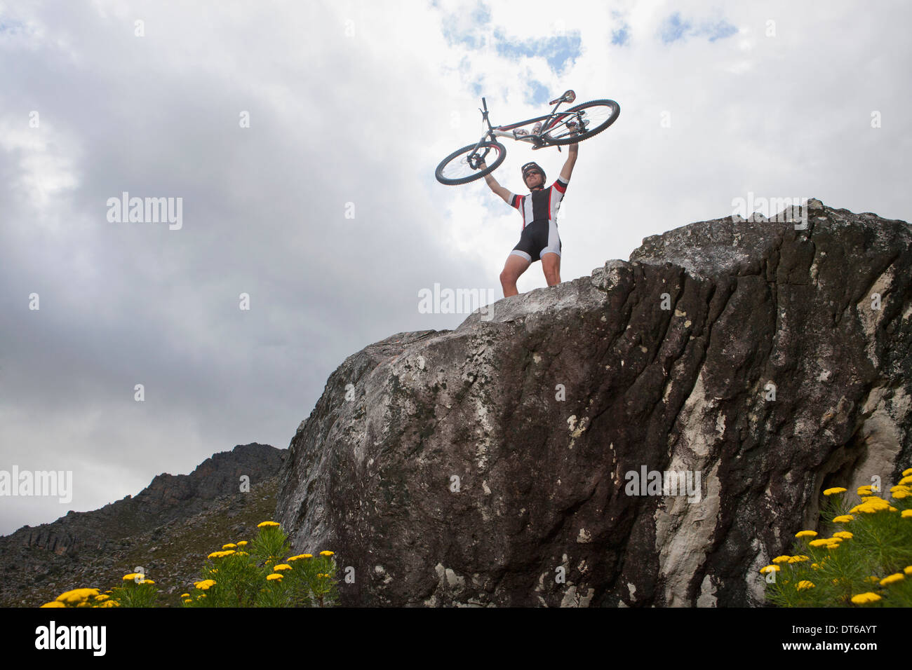 Young man holding up mountain bike on top of rock - Stock Image