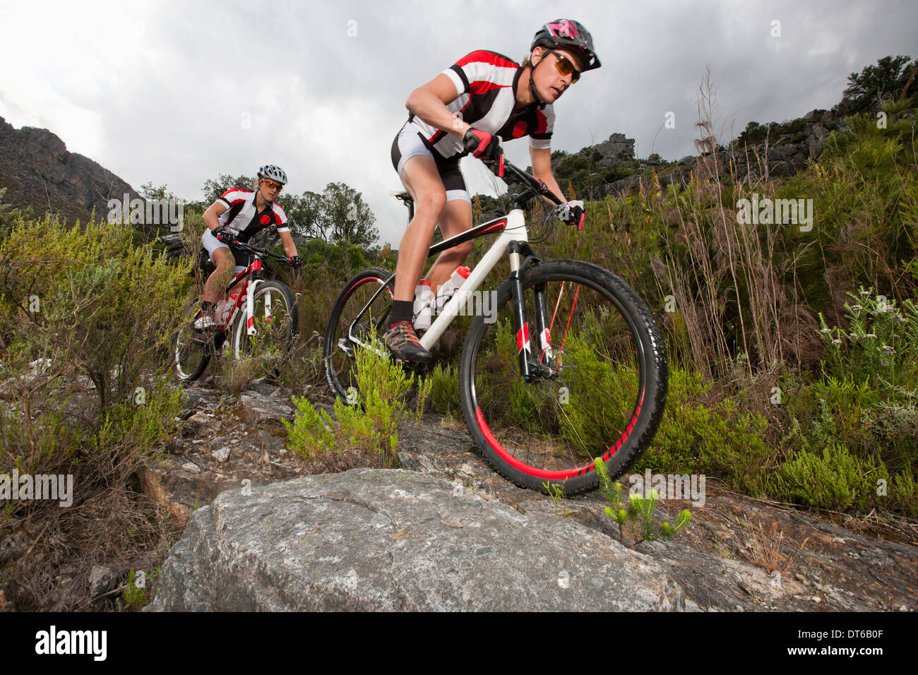 Young couple riding mountain bikes on dirt track - Stock Image