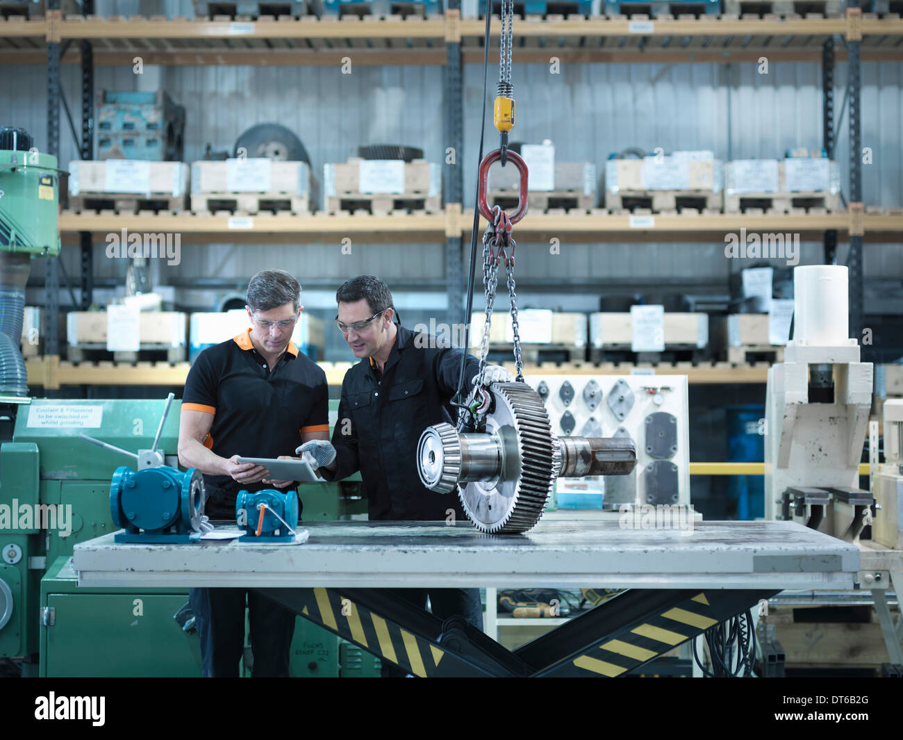 Engineers using digital tablet with gear wheel at work station - Stock Image