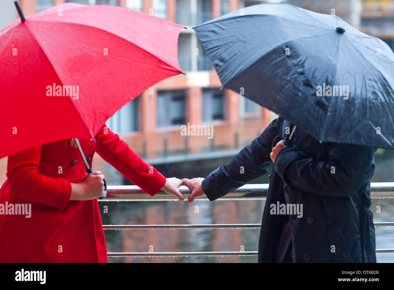 Symmetrical couple holding handrail and carrying umbrella's - Stock Image