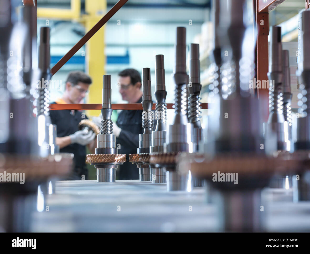 Engineers with parts in industrial gearbox factory - Stock Image