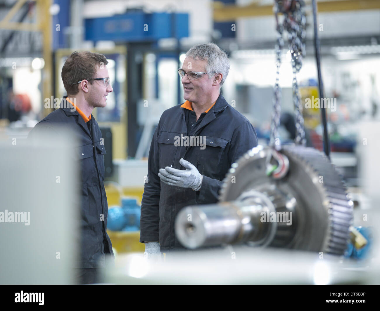 Engineer and apprentice in discussion next to gear wheel at work station in factory - Stock Image