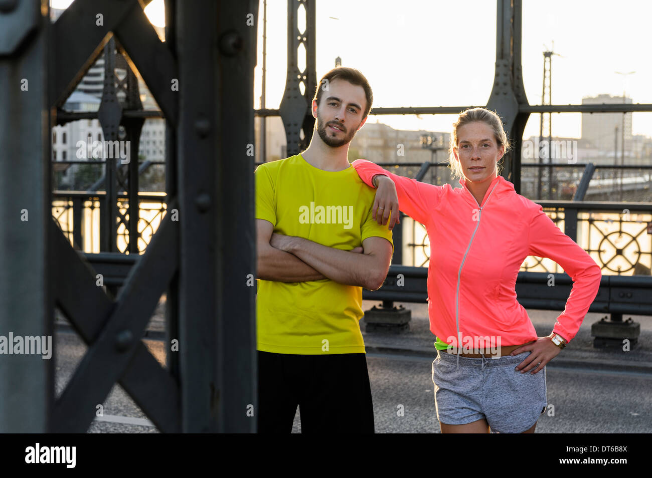 Portrait of young running couple on bridge - Stock Image