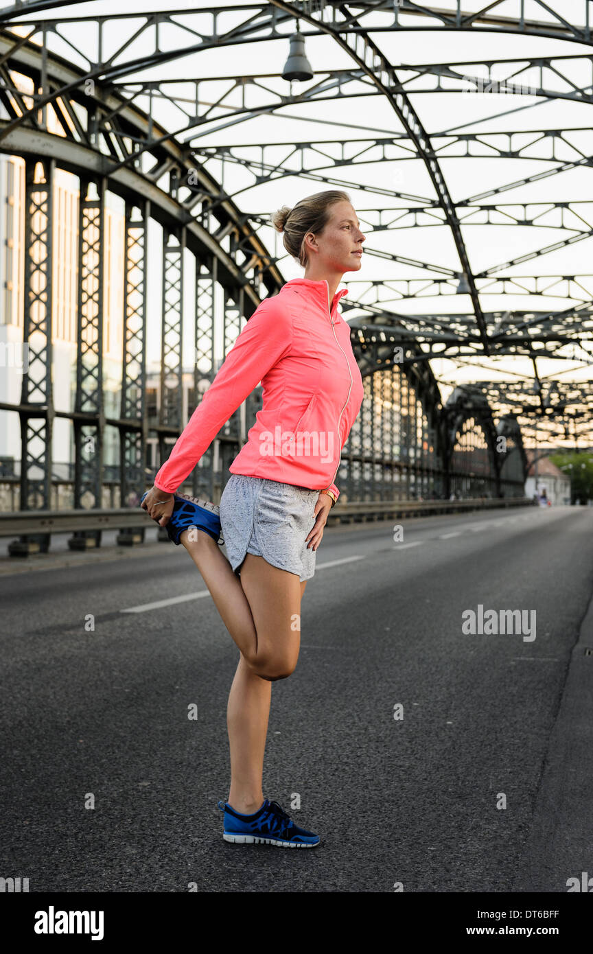 Young female runner stretching on bridge - Stock Image