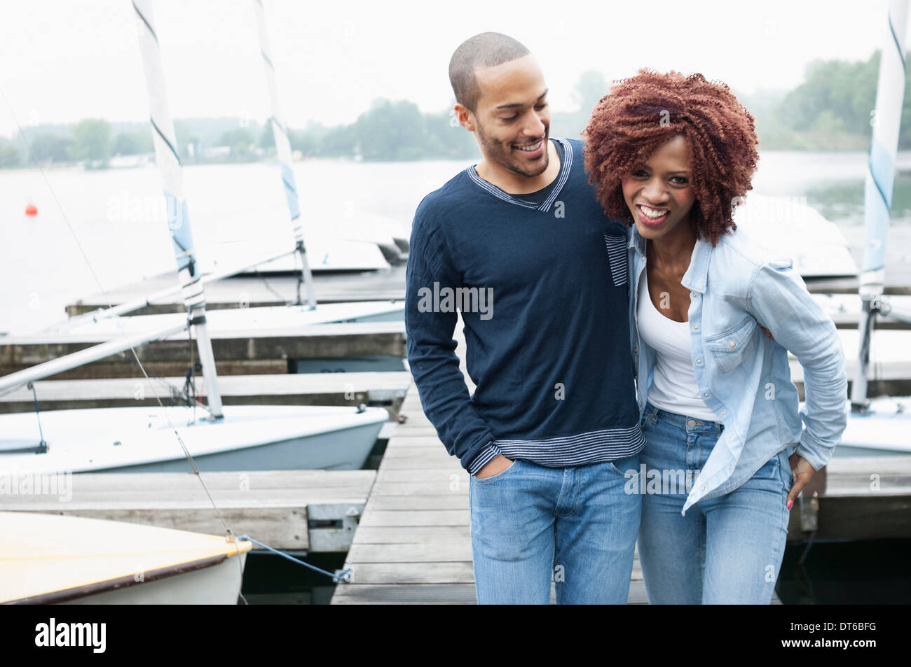 Young couple on jetty laughing - Stock Image