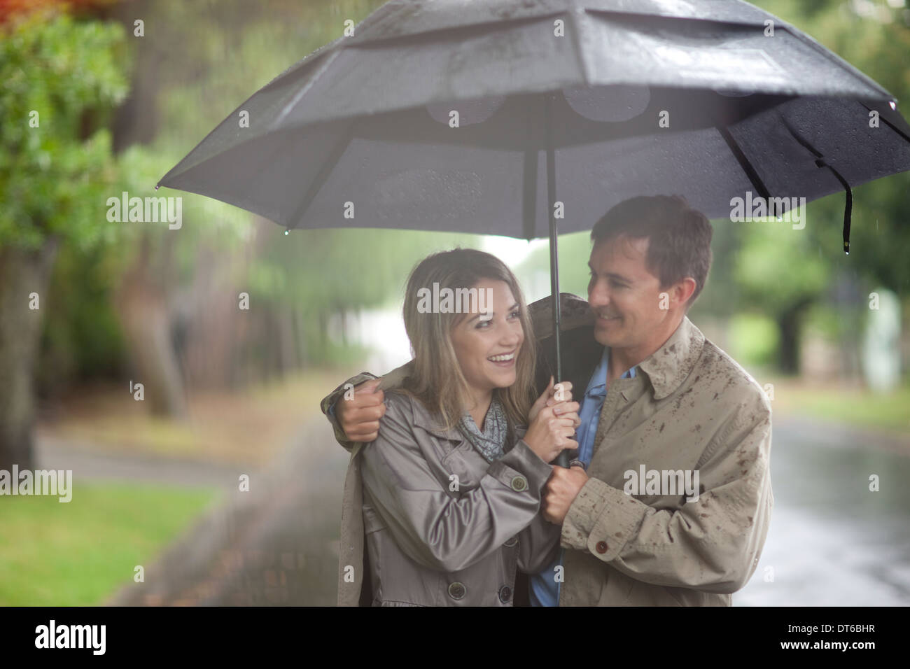 Young woman and mature man walking in rainy park - Stock Image