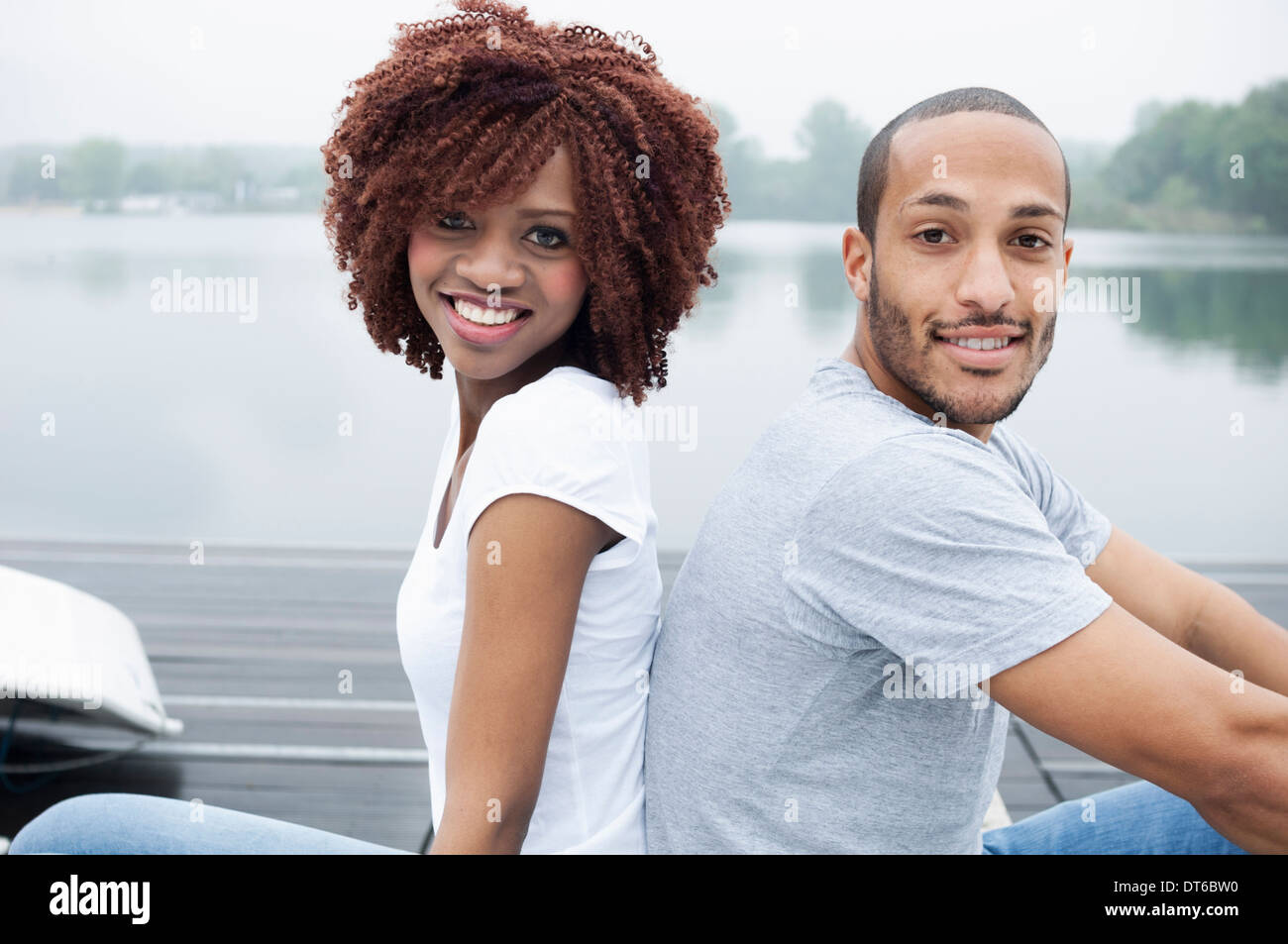 Portrait of young couple smiling, back to back - Stock Image