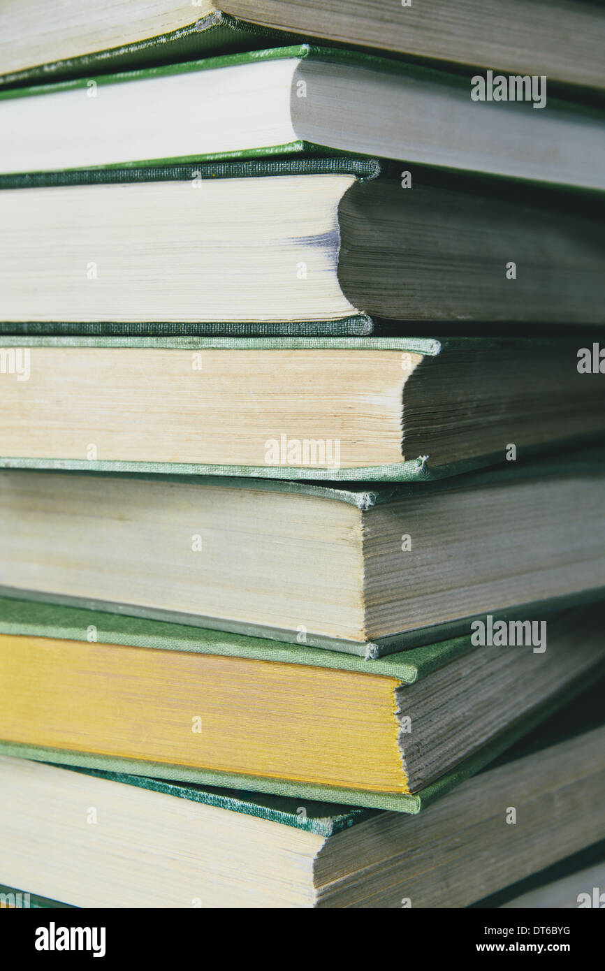 A stack of old hard cover books, with worn edges and paper that is stained or yellowed with age and use. - Stock Image