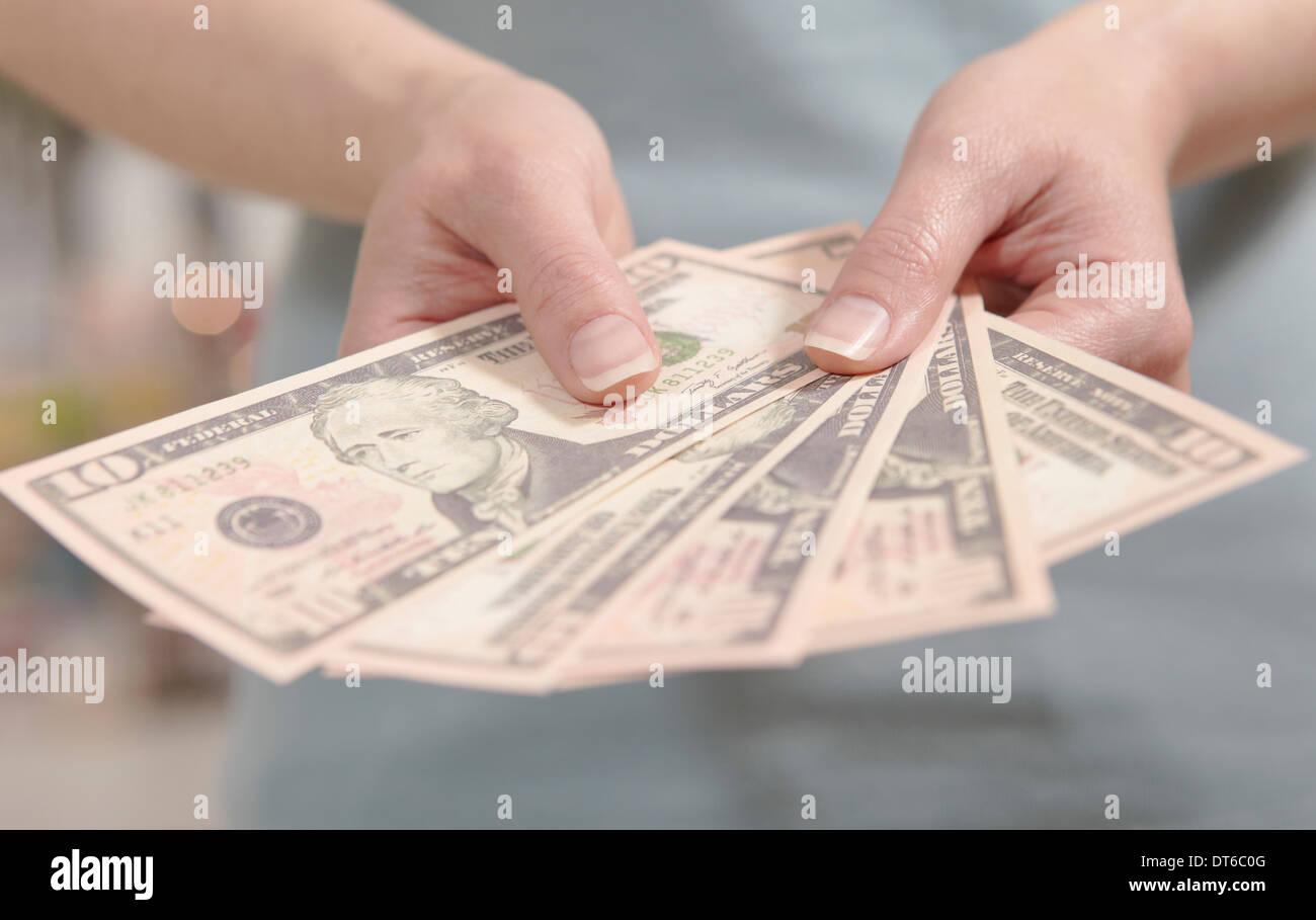 Female hands holding ten dollar notes - Stock Image