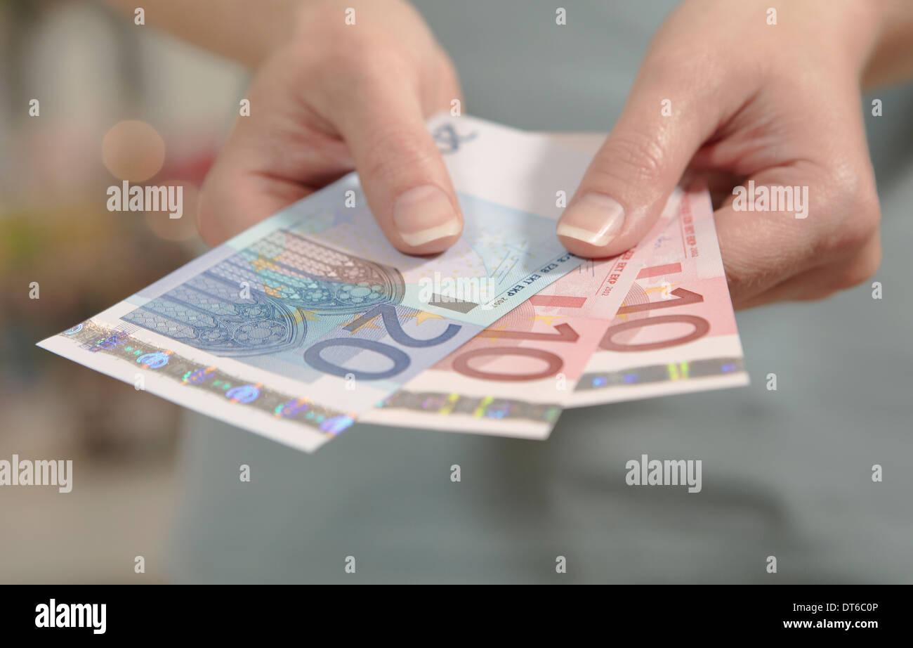Female hands holding ten and twenty euro notes Stock Photo