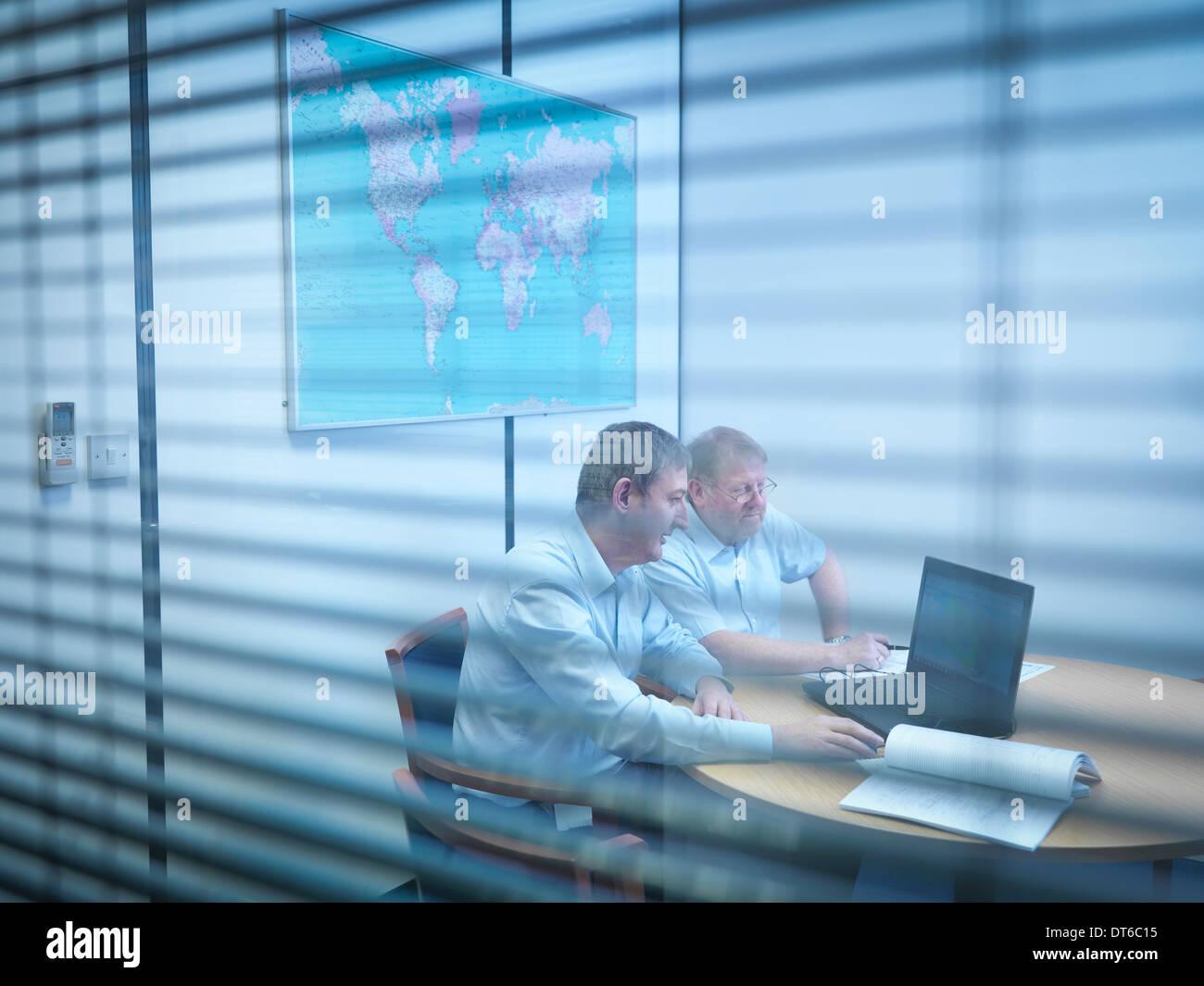 Engineers using laptop in meeting room - Stock Image