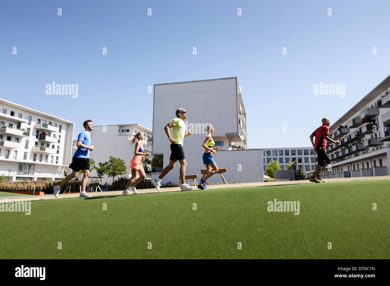 Mature trainer running with small group of adults in park - Stock Image