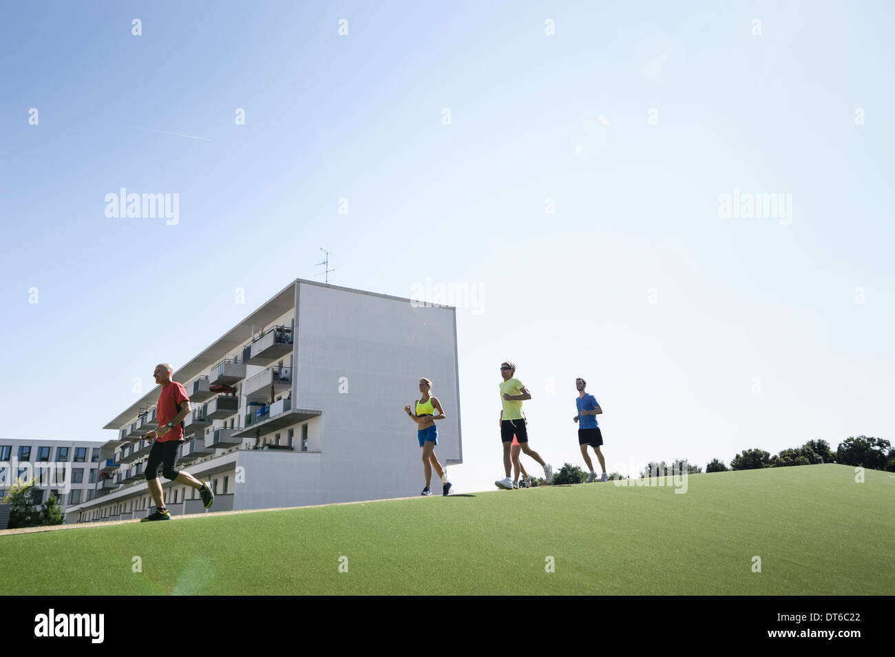 Mature trainer running with small group of adults - Stock Image