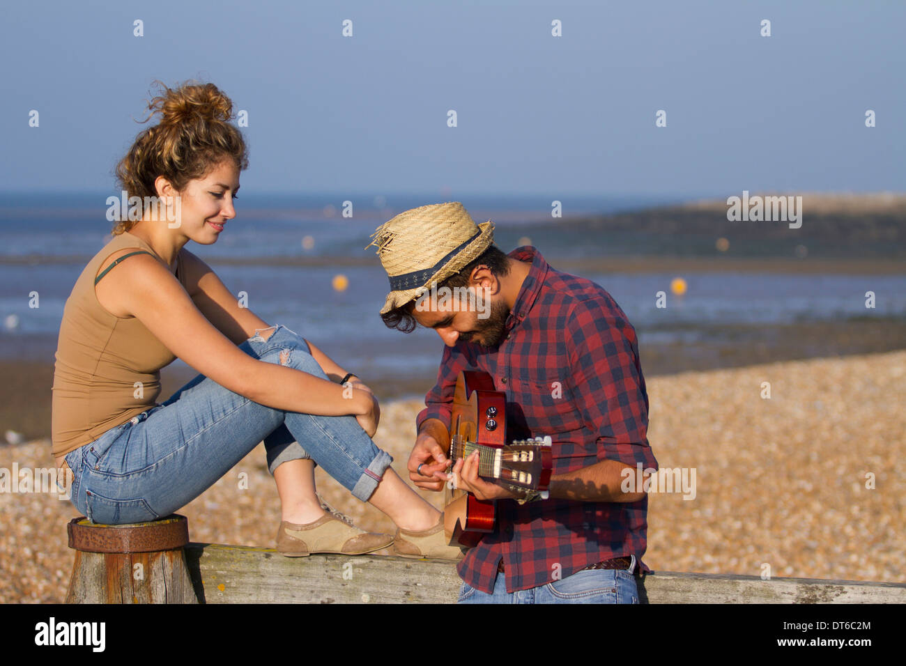 Young couple on beach, man playing guitar - Stock Image