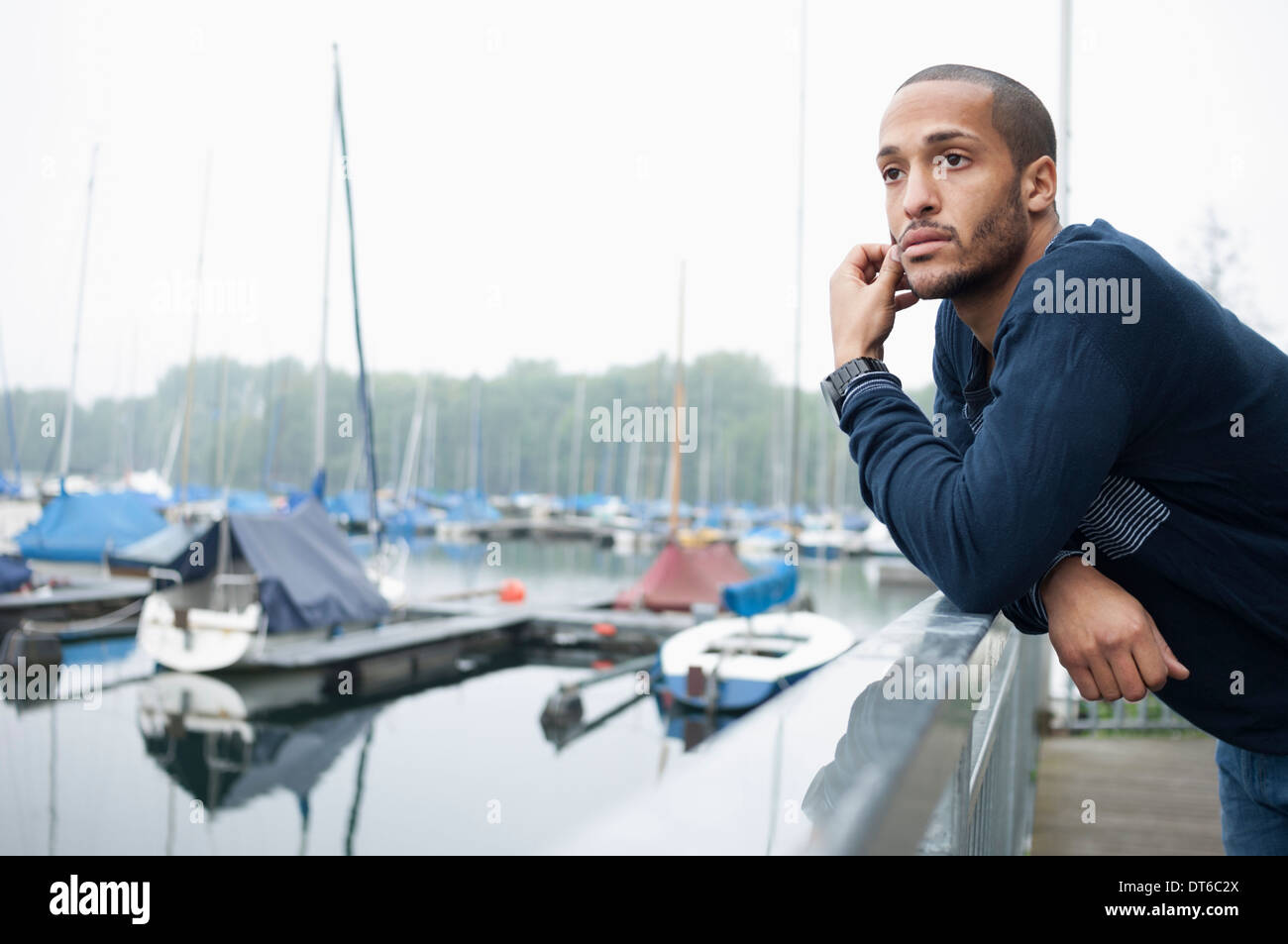 Portrait of young man in marina - Stock Image